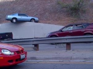 Невероятное ДТП стало причиной удивления жителей американского города Лос-Анджелес: очевидцы инцидента не могли поверить в случившееся. Как сообщает echoru.com, 8 сентября водитель автомобиля в результате уникальной аварии непонятным образом буквально «взлетел» на весьма высокое бетонное ограждение и повис на нем. Хотя машина находилась в весьма шатком положении, машина все же удержалась и не рухнула вниз.